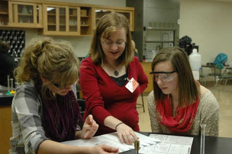 Student teacher Kelly Book explains some of the lab work to juniors Kaylee Newland (left) and Rose Mintkenbaugh (right).  Fitzgerald and Book agreed that the hardest part of the lab is writing out the chemical equations based on what the students have observed in the lab. Photo by McKenna Click.