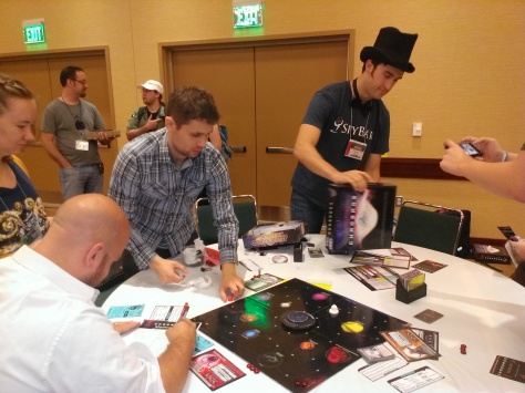 Marketer Sam Vest, in top hat, and game designer Joey Vigour, on the left, oversee a game test. Photo by Garland Noel