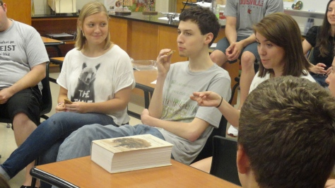 Senior Ben Denison eats a cookie while seniors Sarah Henry and Elaine Colomb joke around him. Photo by Will Huston