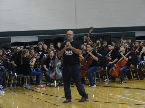 "Orchestra director Doug Elmore addresses the crowd before the Highland Hills sixth grade orchestra plays ""Low Rider"" by War. The sixth graders have no stands because they memorized the entire arrangement.  Photo by Garland Noel."