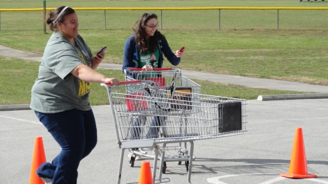 Sophomores Sarah Parker and Chloe Eberly race while texting on their phone. Photo by Delaney Smith