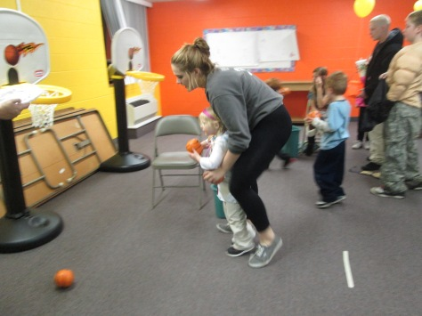 Freshman Kaeyln Gibson helps out a little girl that is attempting to shoot a basketball. Photo by Rachel Lamb
