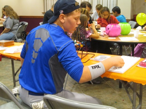 Freshman Chandler Lewis, dressed as a baseball player, calls out numbers during a bingo game. Photo by Rachel Lamb