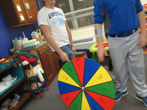 Freshman Dustin Ramsey spins a wheel to win candy. Photo by Rachel Lamb