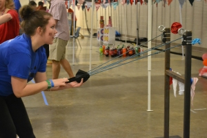 Senior Brittany Harris launches a ball from the catapult at the upstairs carnival booth. Photo by Meghan Poff.