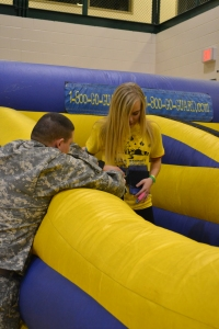National Guardsman Eric Morath helps freshman Emily Jecker strap into a harness for the inflatable  bungee pull. Photo by Meghan Poff.