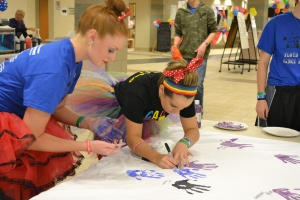 Seniors Scarlett Hartlage and Kelsi Dempster place their handprints on a tarp to commemorate their participation in the marathon. Photo by Meghan Poff.