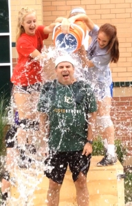 Sophomore Madelyn Weber and junior Kayli Dempster pour a bucket full of ice water on volleyball coach Bart Powell.