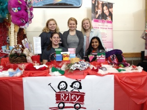 "Seniors Mary Hayes, Emily Naville, Sydney Davis, and juniors Kristen Burger and Anjali Sivamohan pose for a photo as they work the Dance Marathon booth. ""We have this table to raise money for getting a wagon because that's how the kids get around in the hospital in a little red wagon. And they have license plates on them and we are planning on getting one for Floyd Central Dance Marathon so whenever the kids going around in the wagon they all have fcdm on their wagon going to surgery or going wherever they go,"" said Hayes."