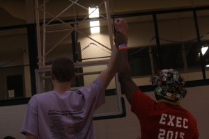Senior Garry Posey raises the hand of dunk contest winner, junior Chase Longest. Photo by Braden Schroeder.