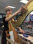 Senior Chelsea Balmer tunes her harp before going to the warm up room.