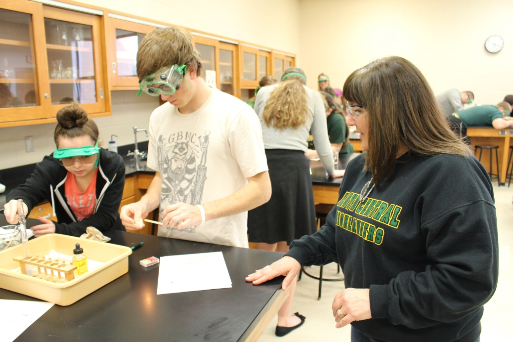 Chemistry teacher Michelle Harbison aids sophomore Emily Dutrow and junior Conner Smith-Sophie during a lab. Photo by Haley Palmer.