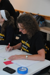 Math teacher and NHS sponsor Melissa Neal writes down information about potential donors.