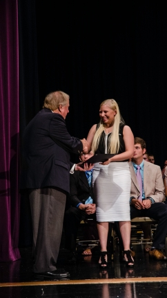 Senior Brittany Hublar shakes hands with a represetative form the Horseshoe Foundation after winning the scholarship.