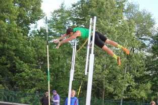 Junior Nicholas Burkland begins to land as he pole vaults.