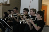 Trumpet players stand in the back and project their music.