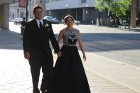 Travis Barger and senior Payton Kruer hold hands as they walk to the Convention Center. Photo by Alaina King.