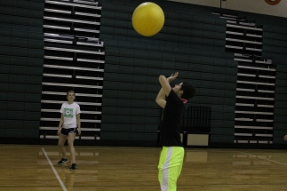Junior Sam Yothers hits a large, yellow ball in a game of volleyball. Photo by Alaina King.
