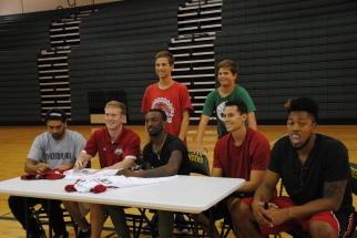 The players pose for photos with campers.
