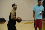 Siva holds the ball and laughs at a comment as current University of Louisville basketball player Zach Price walks by.