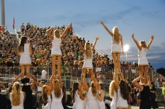 Cheerleaders lift members and wave.