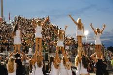 Cheerleaders lift members and wave.