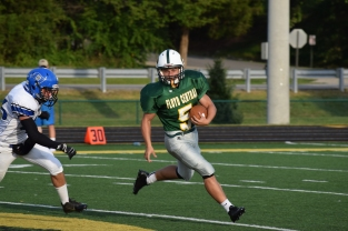 Sophomore Zachary Spurgeon runs the ball away from a Charlestown defender.