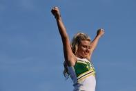 Junior Olivia Babbitt practices her stunts before the game.