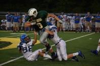 Sophomore Brandon Striegel tries to break the tackles of two Charlestown defenders.