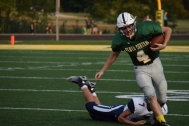 Senior Paden Pikey runs the ball and avoids being tackled.