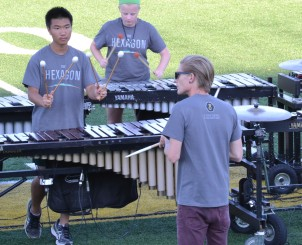 Percussion director Dave Isaacs leads the front ensemble in warm ups before the marching band parent show on Friday, Aug. 21 at Ron Weigleb Stadium.