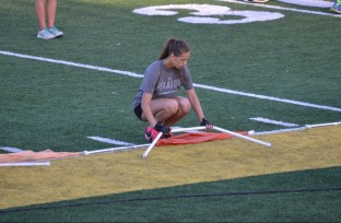Sophomore Dani Halsema bends down to retrieve her half hexagon piece that she spins in the show.