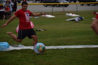"Junior Nik Vellinger kicks the ball while playing ""kiddie pool kickball"" at the FCDM tailgate."