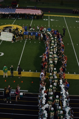 FC students create a tunnel as the football team takes the field.