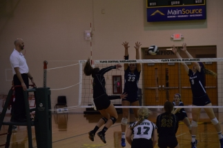 Senior Mikaila Humphrey hits the ball over the net past two Providence players.