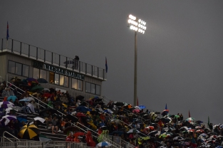 Fans sit under the lights at Ron Weigleb Stadium as it rains during the game against Seymour.