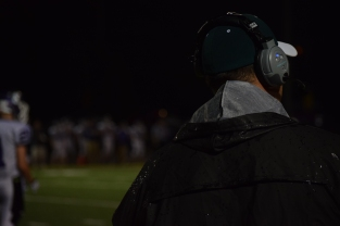 Assistant football coach Dan Derda watches the game from the sidelines.