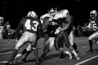A group of Highlanders tackle a Bedford North Lawrence player.