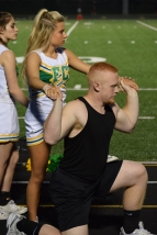 Junior Olivia Babbitt prepares to go up in a stunt while being held by senior Hunter Hampton.