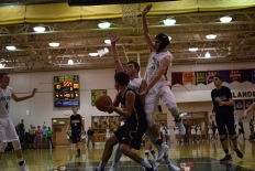 Senior Connor Sturgeon and sophomore Luke Gohmann jump to block the anticipated shot of Henryville sophomore Nick Walker.