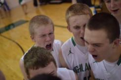 The boys' basketball team gets in a huddle before the start of the game.