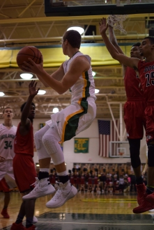 Junior Tyler Kimm passes the ball while under the basket.