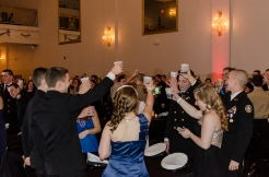 A group of cadets makes a toast to the military, those serving, and soldiers lost in action.