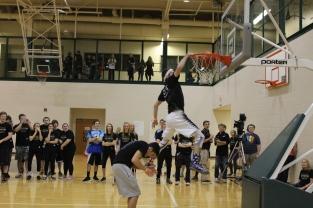 Senior Aidan Flanigan jumps over senior Samuel Yothers as he dunks the ball.