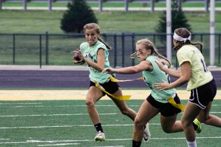Senior Sami Sears moves past several defenders and runs down the field. Photo by Nik Vellinger