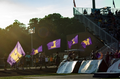 Students from Louisville Male High School student section run with flags boosting the morale of their section before half time. Photo by Robert Wormley