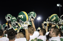 Football players hold their helmets high and do the school fight song after FC defeats Providence 42-6.