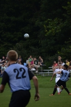 Sophomore Caleb Yankey passes the ball to the front of the net.