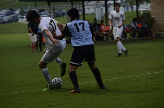 Senior Brodey Zink and Collins High School senior Bryant Ramos fight for the ball.