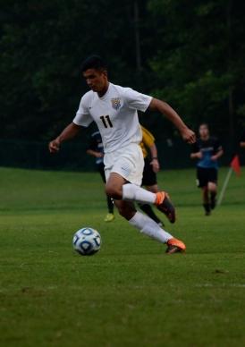Senior Antonio Villegas moves the ball towards the net.